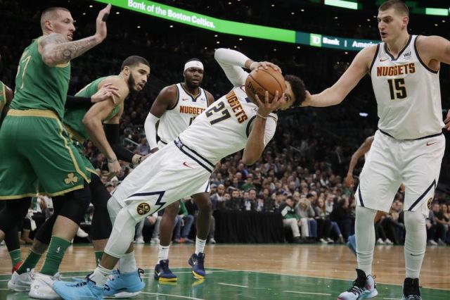 Denver Nuggets guard Jamal Murray (27) looks for an outlet as he falls to the court against the defense of Boston Celtics forwards Daniel Theis (27) and Jayson Tatum, second from left, while Nuggets center Nikola Jokic (15) looks on in the first quarter of an NBA basketball game, Friday, Dec. 6, 2019, in Boston. (AP Photo/Elise Amendola)