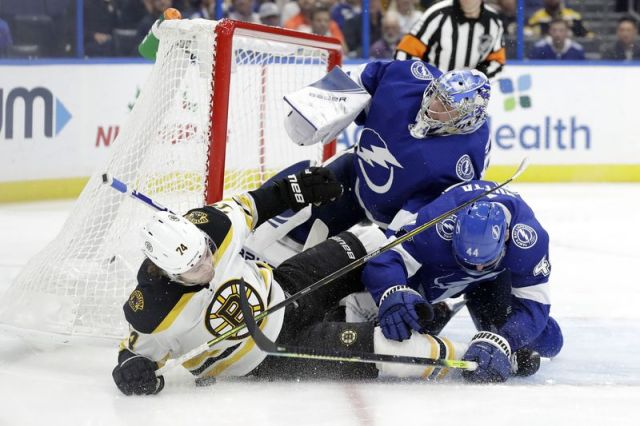 Boston Bruins left wing Jake DeBrusk (74) gets hit by Tampa Bay Lightning defenseman Jan Rutta (44) as they crash into goaltender Andrei Vasilevskiy (88) during the third period of an NHL hockey game Thursday, Dec. 12, 2019, in Tampa, Fla. (AP Photo/Chris O'Meara)