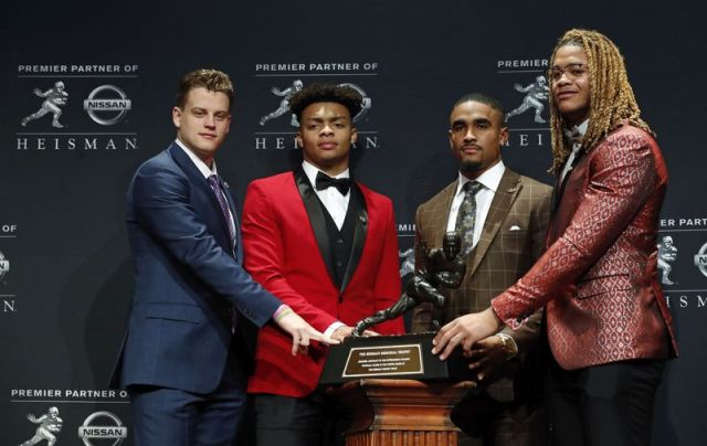 NCAA college football players and Heisman Trophy finalists, from left, LSU quarterback Joe Burrow, Ohio State quarterback Justin Fields, Oklahoma quarterback Jalen Hurts and Ohio State defensive end Chase Young pose for a photo with the Heisman Trophy, Saturday, Dec. 14, 2019, in New York. (AP Photo/Jason Szenes)