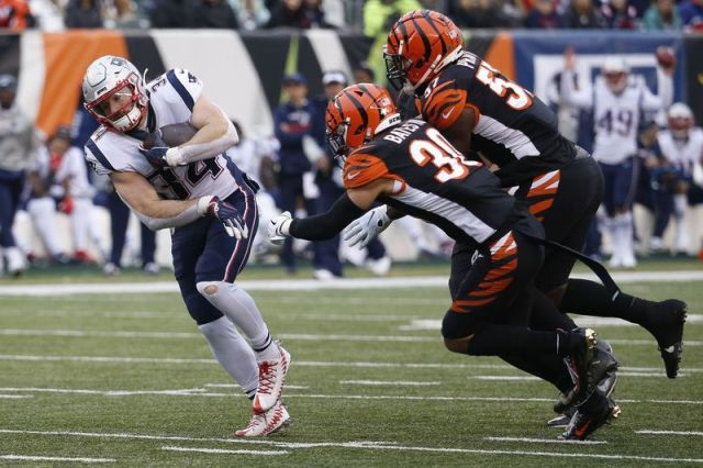 New England Patriots running back Rex Burkhead (34) breaks a tackle on a touchdown run against Cincinnati Bengals free safety Jessie Bates (30) in the second half of an NFL football game, Sunday, Dec. 15, 2019, in Cincinnati. (AP Photo/Frank Victores)