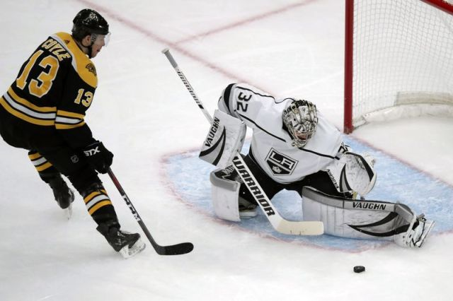 Los Angeles Kings goaltender Jonathan Quick (32) makes a save on a shot by Boston Bruins center Charlie Coyle (13) during the first period of an NHL hockey game in Boston, Tuesday, Dec. 17, 2019. (AP Photo/Charles Krupa)