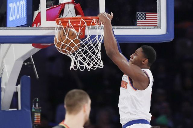 New York Knicks forward RJ Barrett, right, dunks in front of Atlanta Hawks center Alex Len, lower left, during the first half of an NBA basketball game in New York, Tuesday, Dec. 17, 2019. (AP Photo/Kathy Willens)