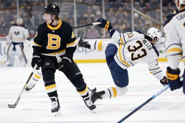 Boston Bruins' Danton Heinen (43) checks Buffalo Sabres' Colin Miller (33) during the first period of an NHL hockey game in Boston, Sunday, Dec. 29, 2019. (AP Photo/Michael Dwyer)