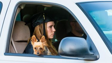 Debra White of East Hartland sits with her dog, Syrah, in her vehicle during Northwestern Connecticut Community College's graduation ceremonies Thursday at Five Points Center for the Visual Arts in Torrington. White graduated from the nursing program. Jim Shannon Republican-American