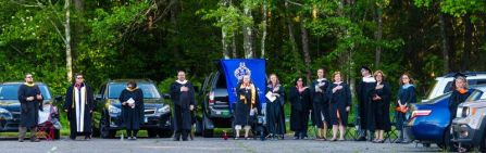College staff members stands for the national anthem while graduates sit in their vehicles during Northwestern Connecticut Community College's drive-thru graduation ceremonies Thursday at the Five Points Center for the Visual Arts in Torrington. Jim Shannon Republican-American