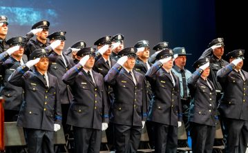 Recruits from the Waterbury Police Academy Class 2020-01 salute as Waterbury Police Det. Andrea Saunders sings the National Anthem during basic training graduation ceremonies Tuesday at the Palace Theater in Waterbury. Jim Shannon Republican American