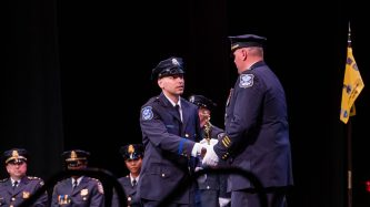 Waterbury Police Academy recruit Damian Velez received the Hanley Award for marksmanship from Sgt. Joseph Ballance during basic training graduation ceremonies for the Waterbury Police Academy Class 2021-01 Tuesday at the Palace Theater in Waterbury. Jim Shannon Republican American