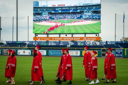 Northwestern Regional High School graduates make their way to their seats from the outfield during graduation ceremonies Wednesday at Dunkin' Donuts Park in Hartford. Jim Shannon Republican American