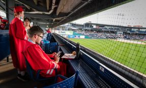 Northwestern Regional High School graduate Jack Johnson checks his phone while seated in the upper deck over looking the field prior to graduation ceremonies Wednesday at Dunkin' Donuts Park in Hartford. Jim Shannon Republican American