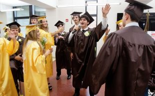 Anthony Mella leads fellow graduates in a few songs to warm them up for their ceremony at Thomaston High in Thomaston Wednesday. Steven Valenti Republican-American