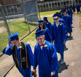 Graduates march to the field during graduation ceremonies Friday at Oliver Wolcott Technical High School in Torrington. Jim Shannon Republican American