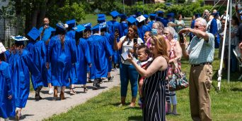 Parents, friends and family members line up to photograph their loved ones as they make their way past during graduation ceremonies Friday at Oliver Wolcott Technical High School in Torrington. Jim Shannon Republican American
