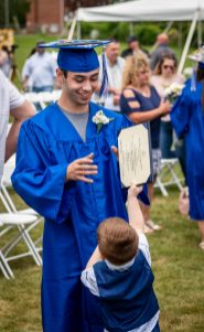"""Oliver Wolcott Technical High School graduate Joesph Kearney, gets his diploma swiped by his nephew Mason Russell, 4, following graduation ceremonies at the school in Torrington on Friday. Kearney, who graduated from the Collision, Repair and Refinishing program, told his nephew """"do you know who hard I had to work for that"""". Jim Shannon Republican American"""