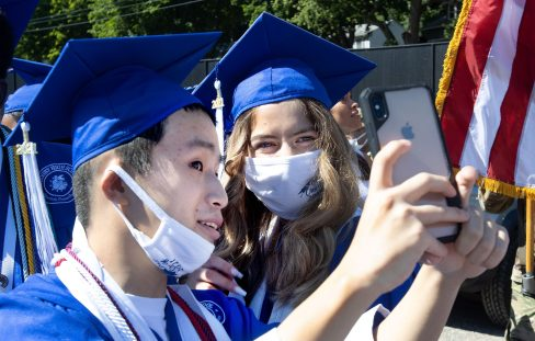 Tommy Jiang, 17, and Livia Dragoj, 17, take a photo together during the Crosby High graduation at Municipal Stadium in Waterbury Thursday. Steven Valenti Republican-American