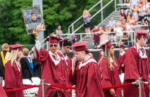 Torrington High School graduate Madè Fajar hols a photo of Kristopher Gomez during graduation ceremonies on the Torrington High School football field on Friday. Gomes was a junior and only 16-years-old when died in 2020 after suffering a stroke. Jim Shannon Republican American