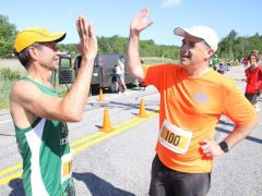 Mike Main, left, and Peter Vermilyea, both of Litchfield, exchange a high-five after finishing the Litchfield Hills Road Race on Sunday. John McKenna Photo