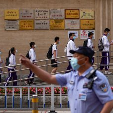 """A police officer gestures as students wearing face masks to help curb the spread of the coronavirus line up to enter a school for the first day of China's national college entrance examinations, known as the """"gaokao,"""" in Beijing, Monday, June 7, 2021. More than 10 million high school students throughout China will take the two-day annual college entrance exams, according to state media. (AP Photo/Andy Wong)"""