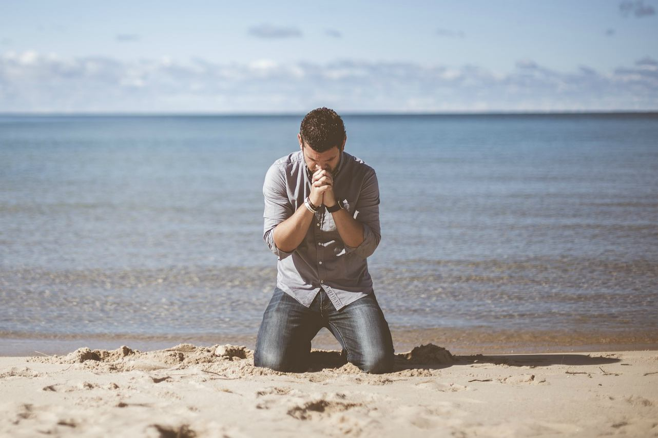 An image of a man praying on his knees on a beach
