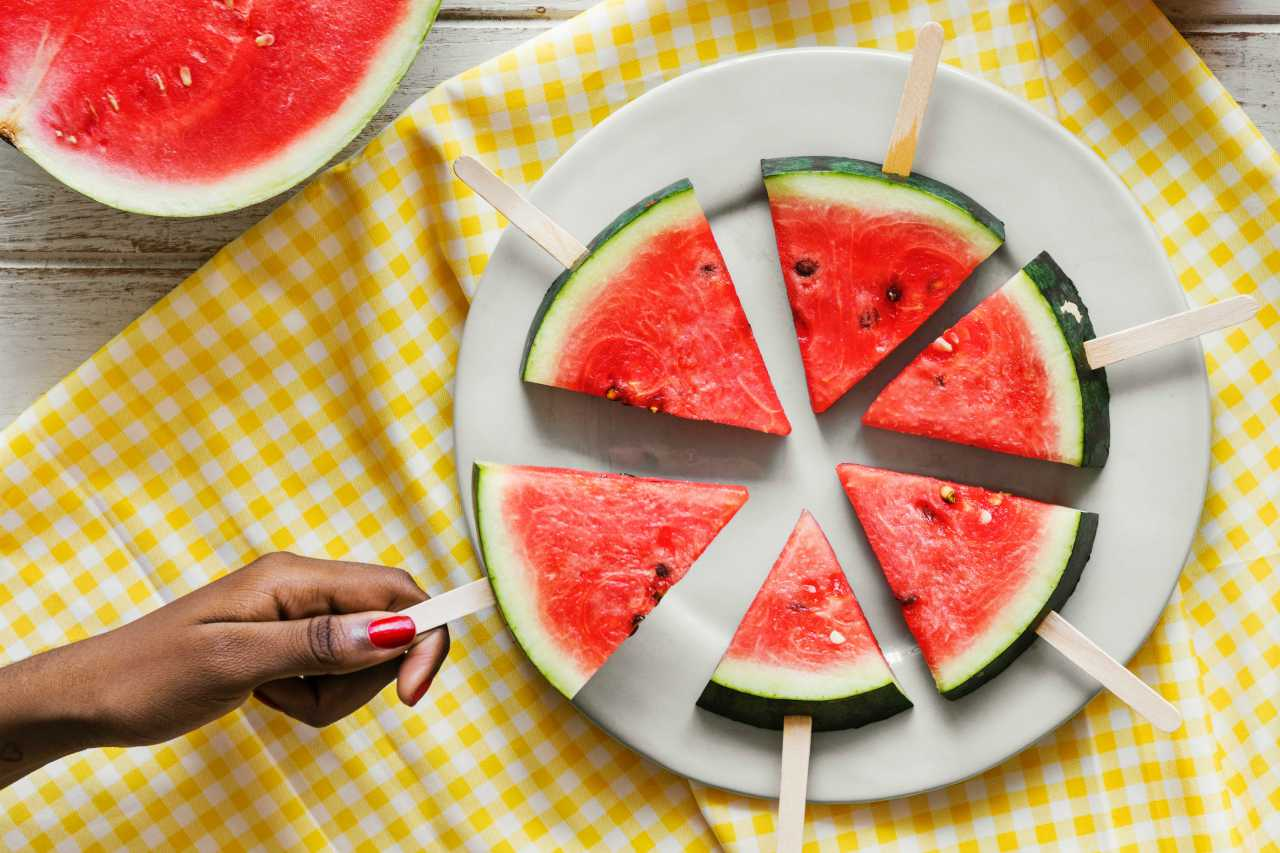 An image of a woman taking a piece of watermelon sliced into triangles