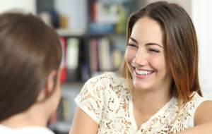an image of Happy woman talking and laughing with a friend at home