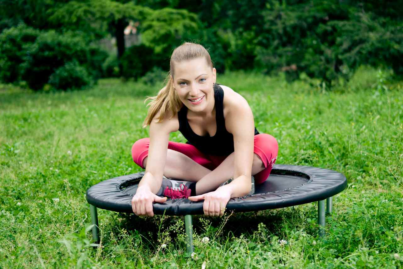 An image of a woman sitting on a rebounder in a field
