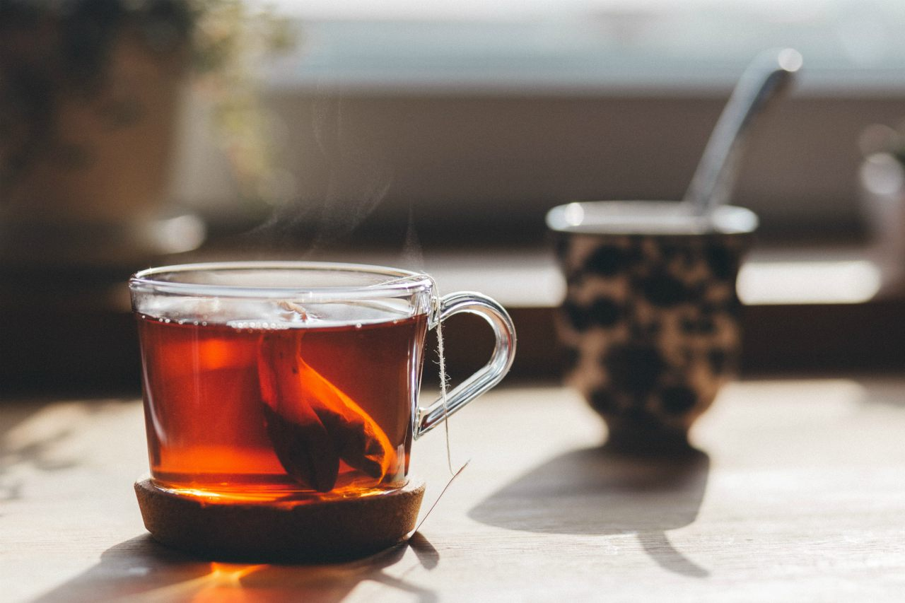 An image of a glass mug containing dark tea