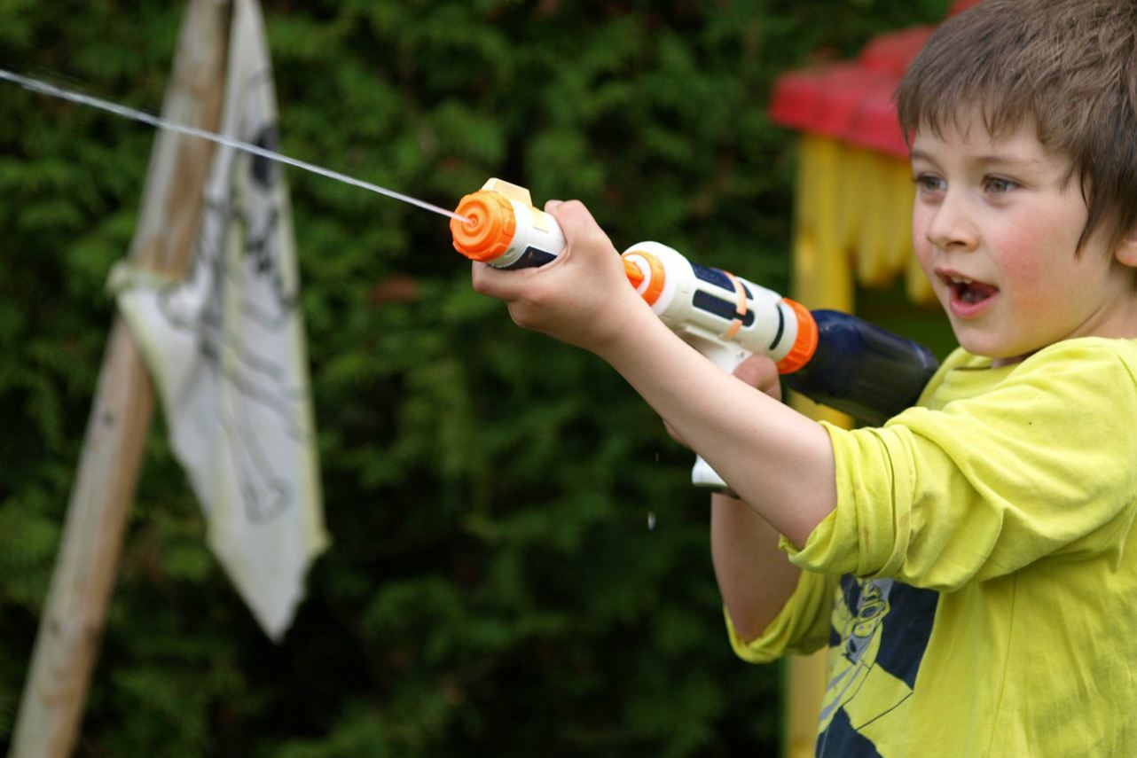 An image of a child using a water gun outside
