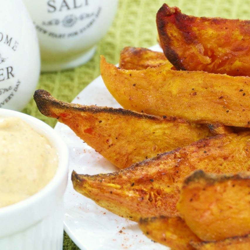 An image of a plate of spicy sweet potato wedges and a bowl of chipotle mayo