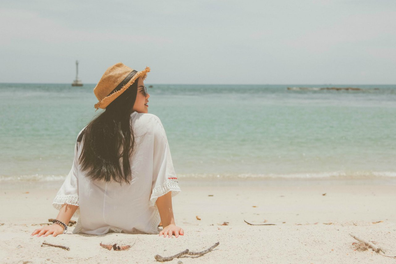 An image of a woman wearing a hat sitting on a beach