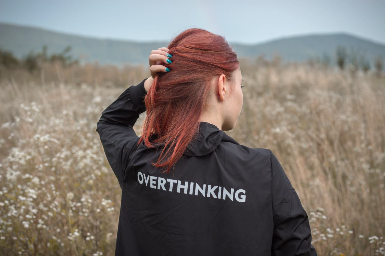 An image of a woman standing in field wearing a jacket that says overthinking
