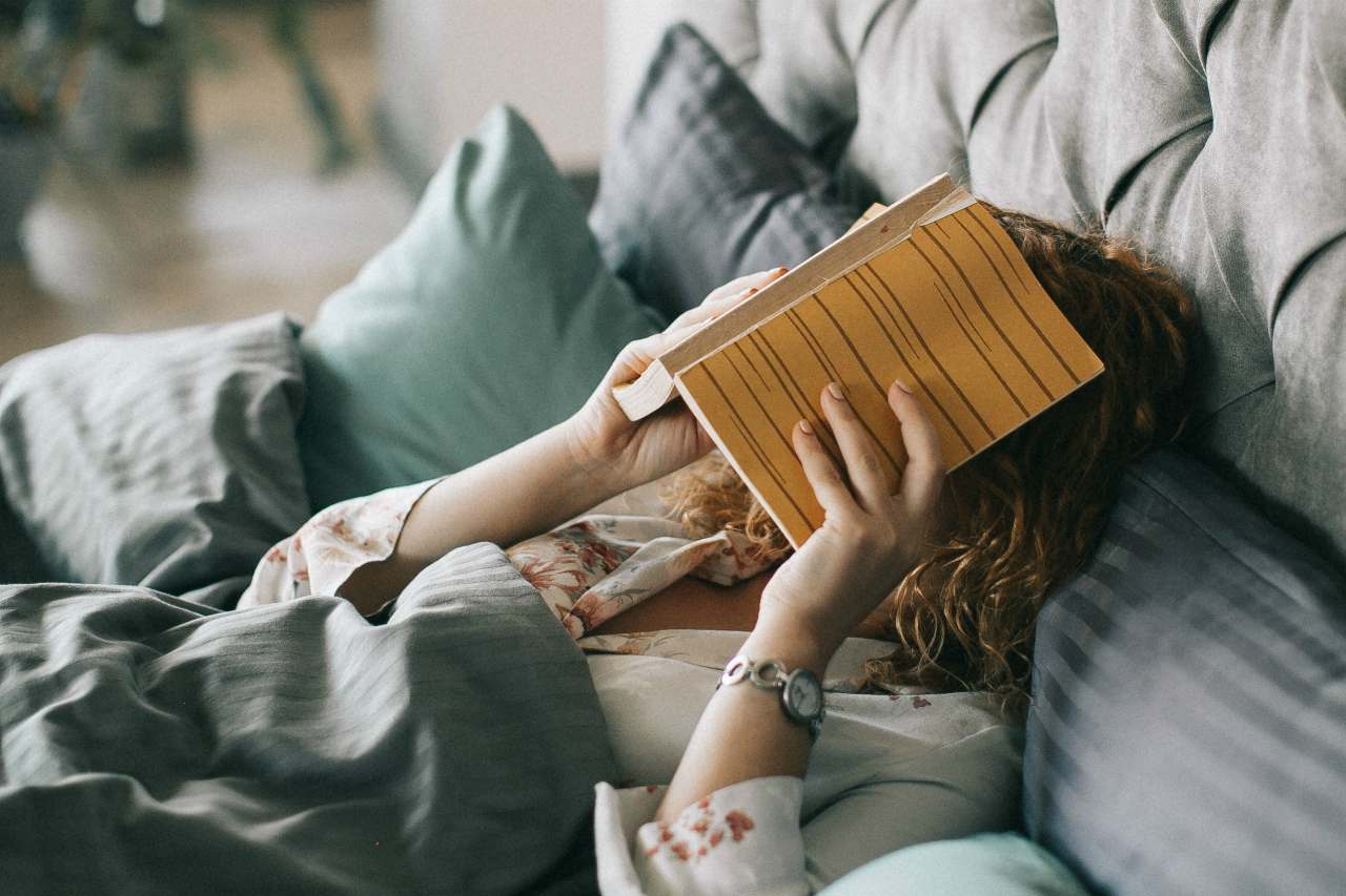 An image of a woman in bed covering her face with a book