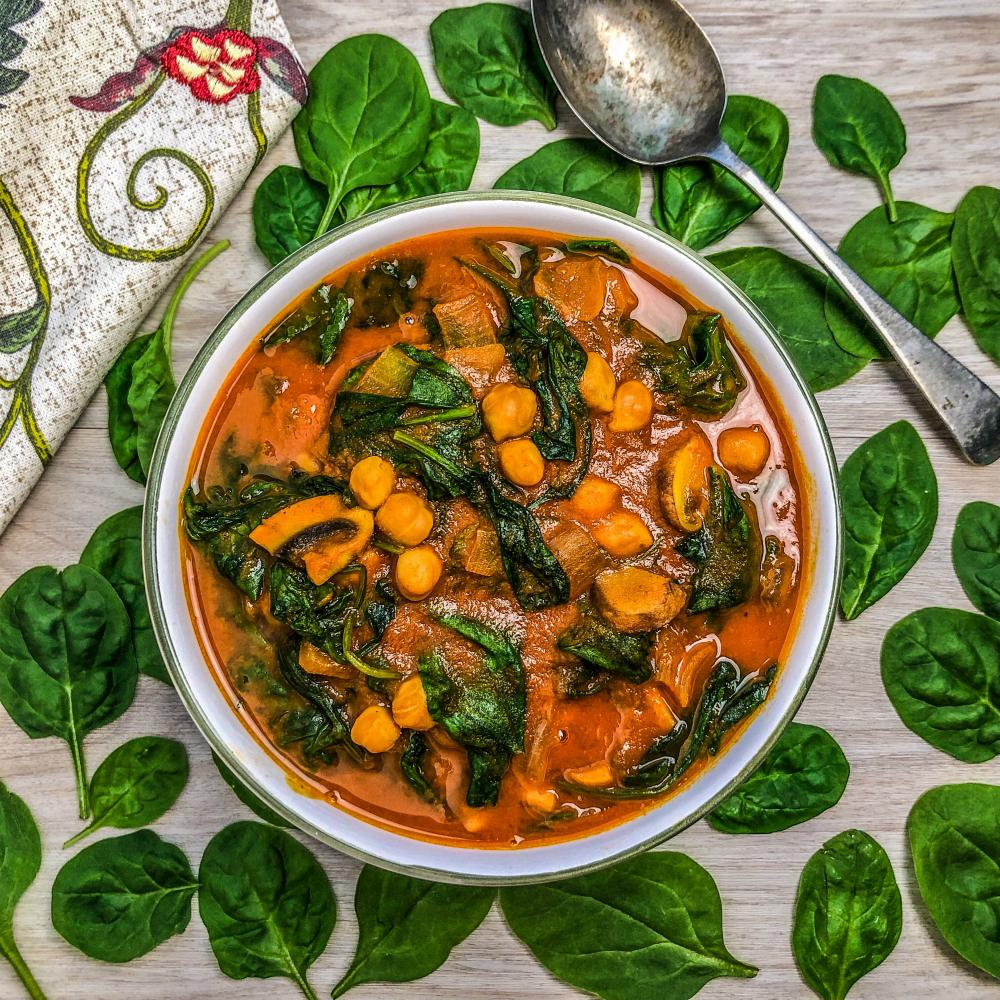 An image of a bowl of spinach, mushroom, chickpea curry surrounded by fresh spinach leaves.