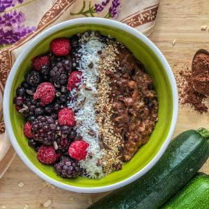 An image of a bowl of chocolate zucchini oatmeal topped with berries, coconut, and sesame seeds.