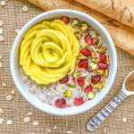 An image of a bowl of vanilla chai overnight oats topped with a mango rose, pomegranate seeds, and chopped pistachios.