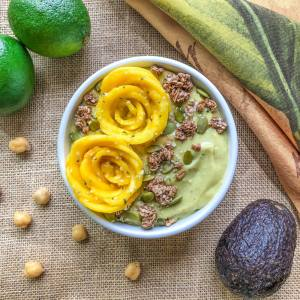 An image of a key lime pie smoothie bowl topped with mango roses, granola, pumpkin seeds, and hemp seeds.