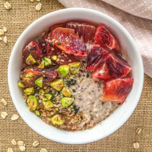 An image of spiced blood orange overnight oats topped with sliced blood orange, chopped pistachios, hemp hearts, and some ground spices.