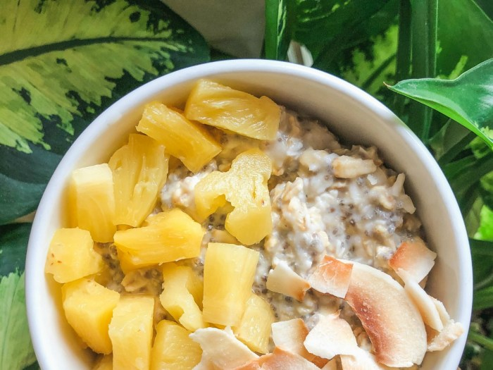 An image of a bowl of pina colada overnight oats topped with diced pineapple and coconut.