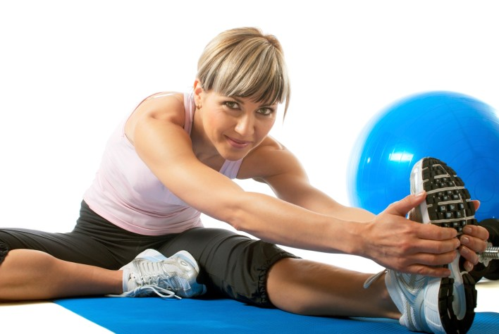 Young beautiful sportswoman stretching on a mat.