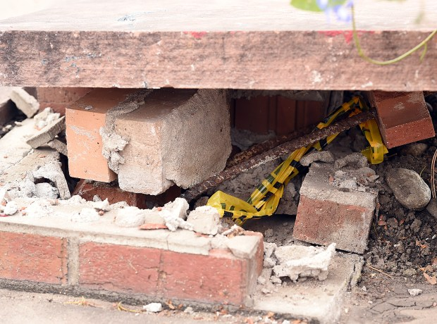 A smashed brick column enforced with rebar rests on the ground Wednesday. A car plowed through the columns and landed on a table where a family was sitting Saturday in Loveland. (Jenny Sparks / Staff Photographer)