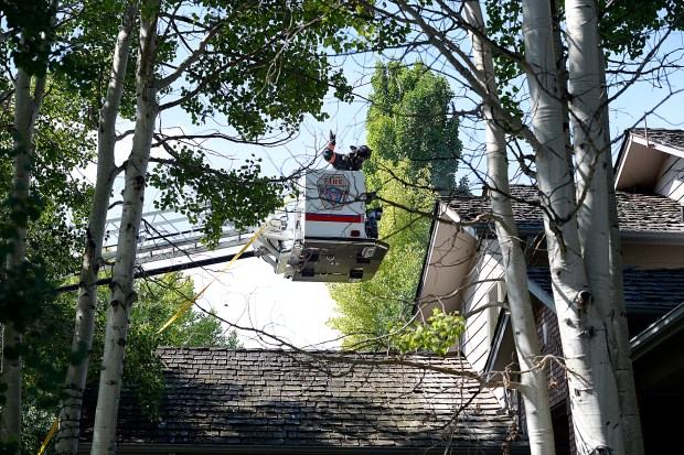 LOVELAND, CO-July 5, 2019: A Loveland Fire Rescue Authority firefighter gets a closer look at the roof and attic of a house as crews fight a fire at the house, 3079 Kiowa Dr., Friday, July 5, 2019, in west Loveland. (Jenny Sparks / Loveland Reporter-Herald)