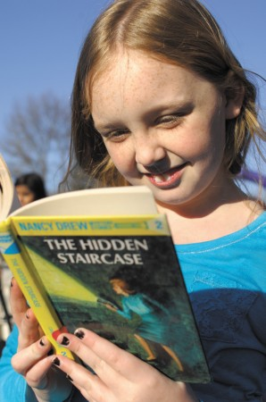 "Arwen Coy, selects a book to read from the ""little library"" in Briarwood Park."