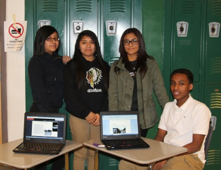 From left, Cross Keys students Dinamis Roblero-Lopez, Cindy Ramirez, Zujey Ramirez and Faysal Ando gather around laptops displaying their Buford Highway presentations. (Photo John Ruch)