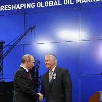 Vladimir Putin embraces his business partner, ExxonMobil chief Rex Tillerson