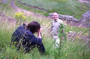 Tony Robinson being photographed by the press in the long grass at the edge of the Roman theatre