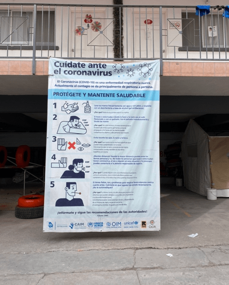 """A banner in Spanish promoting COVID-19 prevention, hanging off of a second floor railing in an old motel that serves as an IRC-supported """"triage hotel"""" in Mexico"""