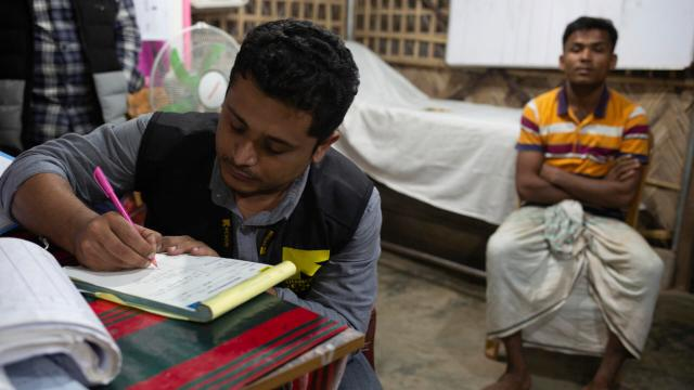 Dr. Mahmudul Hossain, wearing an IRC vest, sits at a desk writing notes. A patient sits behind him.