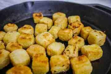 Golden brown crispy tofu in a cast iron skillet