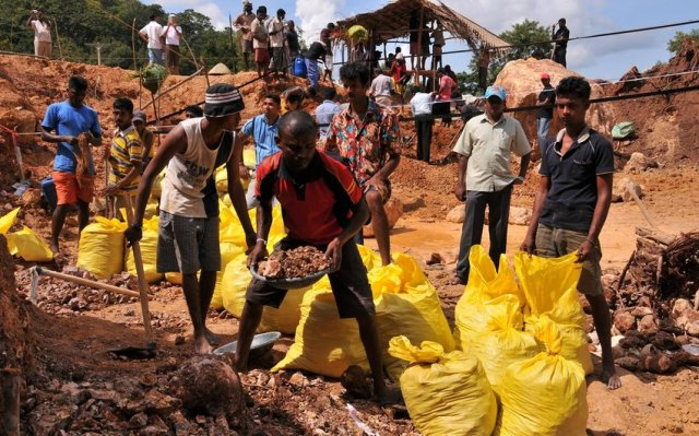 Các thợ mỏ thu thập đất có khả năng chứa sapphire trong các túi để mang đi rửa sạch tìm đá quý. Ảnh: Andrea Heather Go.