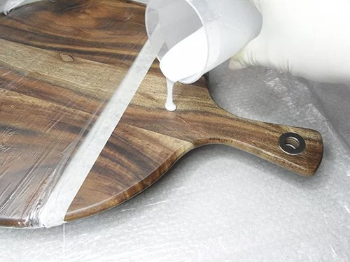 pouring white resin over the cheese board handle