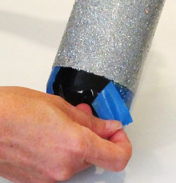 removing painters tape from the bottle of a stainless steel tumbler